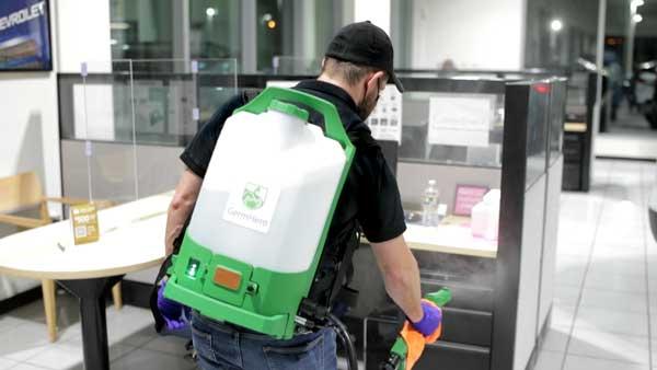 Germ Hero Technician Disinfecting Car Dealership Showroom